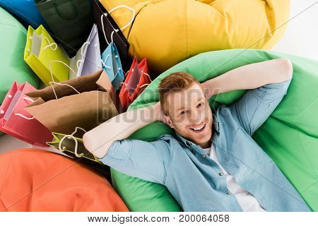handsome smiling man resting in bean bag chair with colorful shopping bags