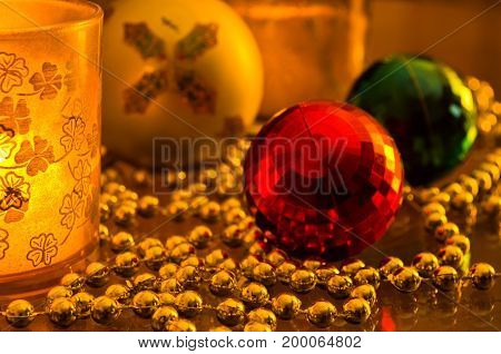 Christmas shiny colored decorations prepared for christmas tree and a glass with a candle