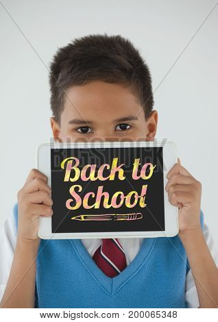 Digital composite of Boy holding a tablet with back to school text on screen