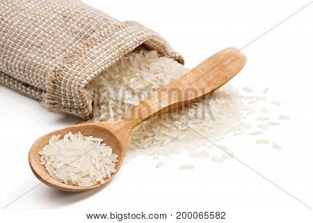 Parboiled rice in wooden spoon and sack with scattered rice on white background. Close up high resolution product