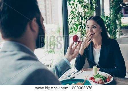 Rear View Of A Brunet Bearded Man Proposing To His Cute Shocked Brunette Lady In A Nice Restaurant W