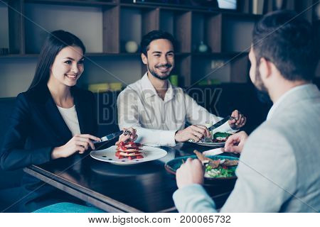 Three Friendly Buiseness Colleagues In Formal Suits Are Sitting In Restaurant And Smiling, Having Ni