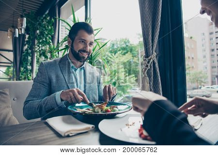 low angle cropped photo of a brunet guy stting in a fancy restaurant`s terrace with view in a formalwear and smiling looking at his lady having salad