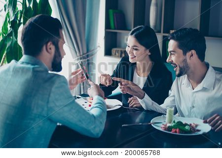 Three Friends Colleagues In Formal Outfits Are Sitting In Restaurant And Pointing At The Brunet`s Gu