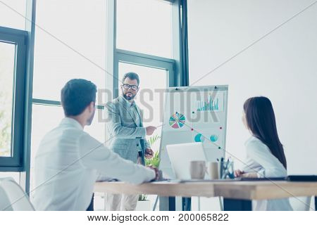 Low Angle Shot Of A Young Smart Brunet Bearded Manager In Spectacles, Reporting To The Team Of Colle