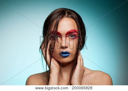 Gorgeous young model with creative make up and hairstyle. Beauty and fashion. Artistic on stage make up