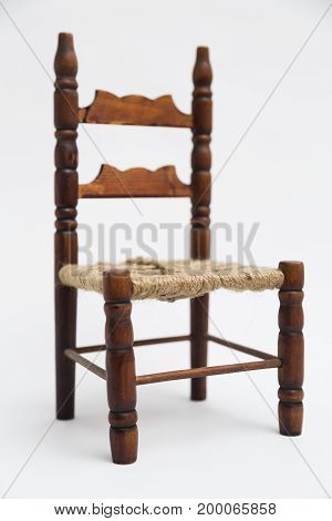 Old vintage wooden retro classic small brown handmade coiled carved elegant chair with decorative elements on white background.
