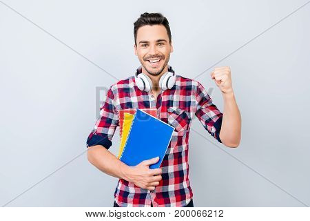 Cheerful Young Brunet Nerdy Student With Stubble Is Standing With Colorful Books On Pure Background
