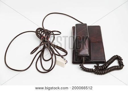 Old vintage stationary shiny leather brown plastic telephone with round dial and a tube on the wire with a long twisted cord on white background.