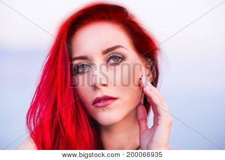 Red hair woman in a blue dress on a seashore