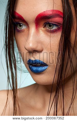 Clos up portrait of beautiful young model with creative make up and hairstyle. Beauty and fashion. Artistic on stage make up