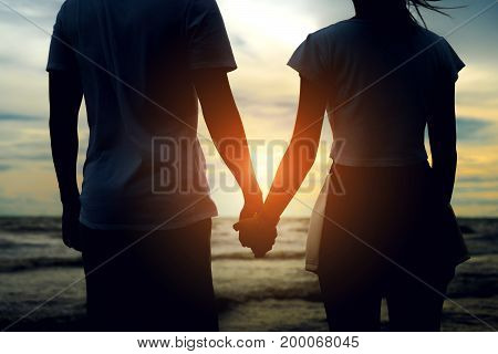 Young asian man holding hand with girl romantic together relationship valantine lover day at beach vacation time leisure back view sunset evening.