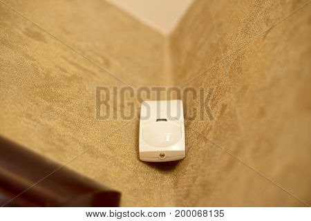 Motion sensor or detector for security system mounted on wall in a house