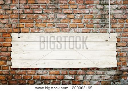 Wooden sign with ropes isolated over brick wall background