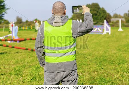 Horse handler take pictures on smart phone