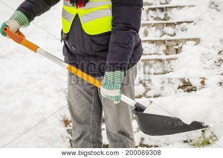 Man shoveling snow on stairs in winter day