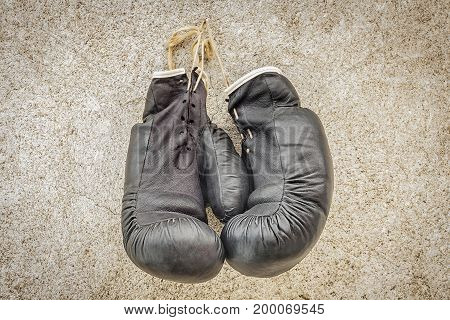 Old boxing gloves on wooden wall .