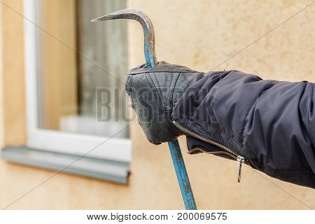Robber's hand with crowbar near the window