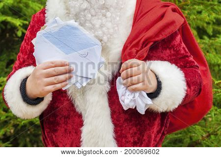 Santa claus with open envelopes and letters