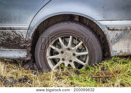 Stuck car in the mud in autumn day