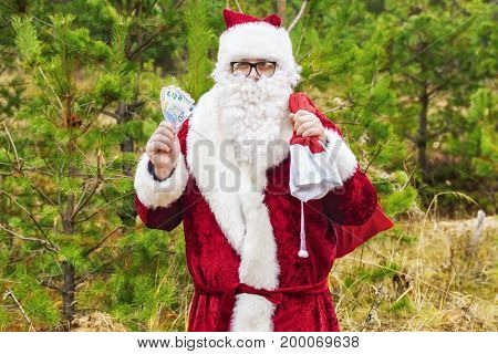 Santa Claus with euro banknotes and gift bag in forest