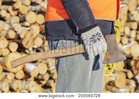 Lumberjack with ax and rope near pile of logs