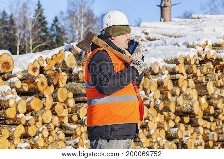 Lumberjack talking on phone near pile of logs