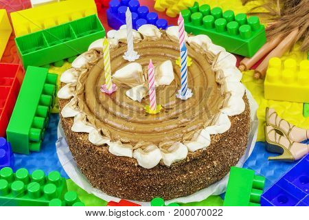 Burning candles in chocolate cake with toy bricks around
