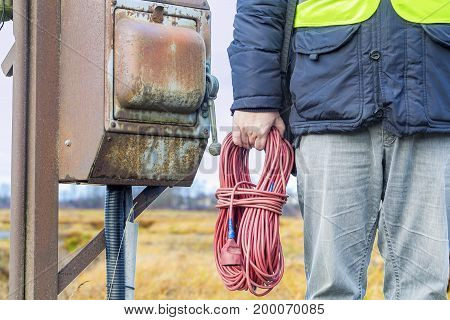Electrician with cable near box in autumn day