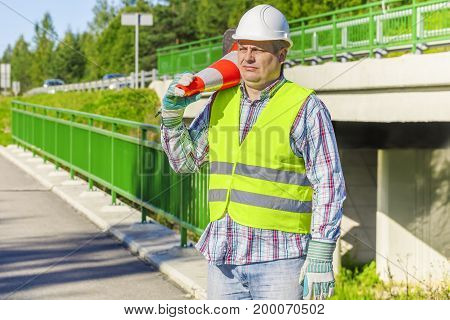 Road construction worker with traffic cone .