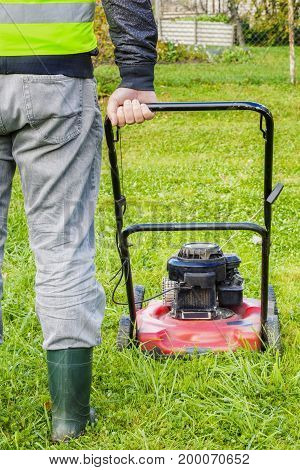 Worker pushing lawnmower in garden in summer day