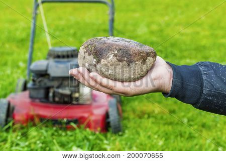 Man's hand with stone before lawn mower