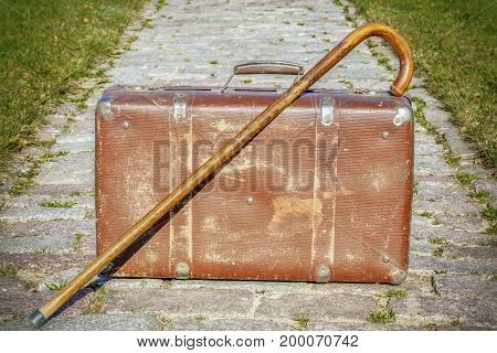 Old suitcase with walking stick in backgrounds
