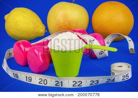 Dumbbells with tape measure,whey powder and fruits on blue