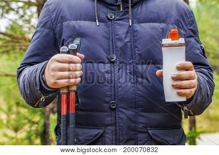 Hiker holding cup with drink and hiking poles