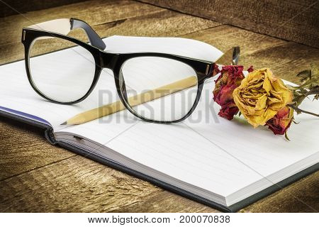 Glasses , notebook , pen and dry roses in backgrounds