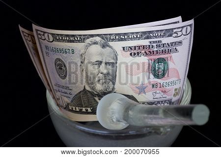American dollars in a glass mortar with a pestle.