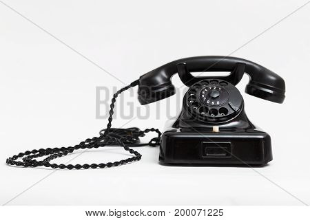 Old vintage stationary shiny black plastic telephone with round dial and a tube on the wire with a long cord on white background