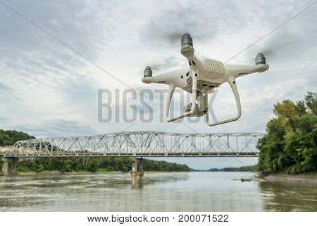 Overton, MO, USA - August 13, 2017S:  DJI  Phantom 4 pro  quadcopter drone flying with a camera over the MIssouri RIver with a highway bridge in background.