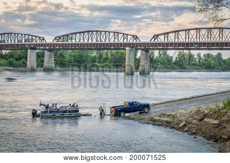 Glasgow, MO, USA - August 13, 2017: Motor boat is being loaded on trailer at a boat ramp after Sunday recreation on the Missouri River.