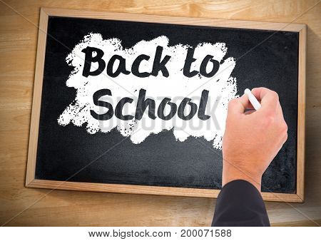 Digital composite of Hand writing back to school on blackboard