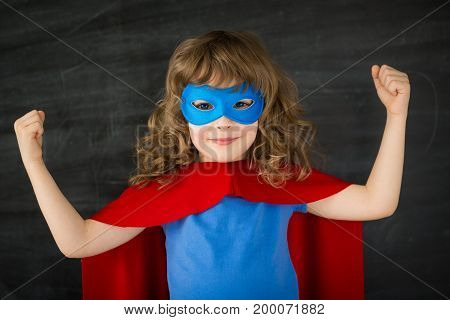 Superhero kid against blackboardю Back to school