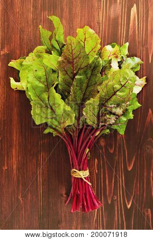 Leaves Of Beetroot In Bouquet On The Brown Wooden Background.