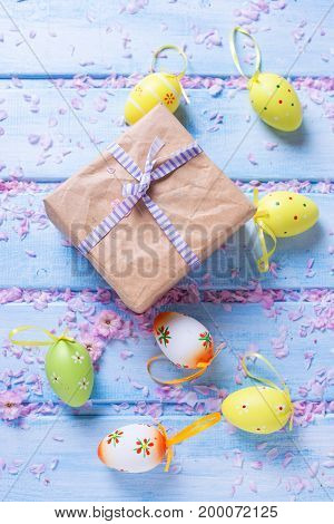 Easter postcard. Box with present bright Easter eggs on blue wooden background. Selective focus is on box.