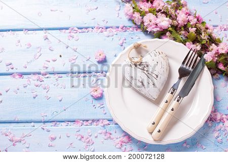 Spring table setting. Pink flowers heart knife and fork on white plate on blue wooden background. Selective focus. Place for text. Top view.