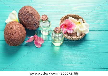 Organic natural spa products. Bottles with coconut oil on bright wooden background. Selective focus. Place for text.