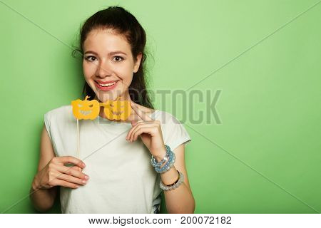 Attractive playful young woman with false party glasses