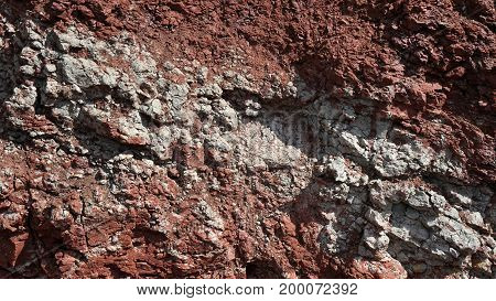 the texture of the red clay wall of a large clay pit