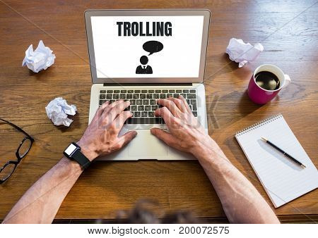 Digital composite of Trolling text and chat icon on laptop with hands