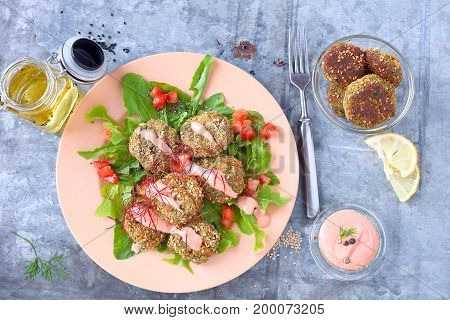 Kale bites with breadcrumbs and sesame seeds with tomato, salad and pink sauce.